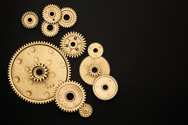 multiple brass gears on a black background
