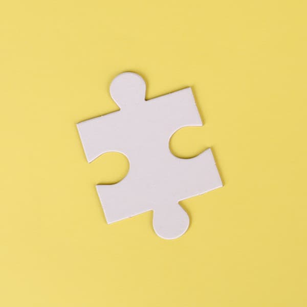white puzzle piece on yellow background